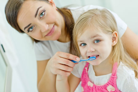 Mom and Daughter brushing their teeth - Pediatric Dentist in Council Bluffs, IA